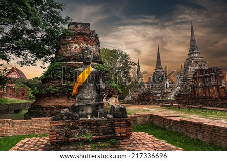 Asian religious architecture. Ancient sandstone sculpture of Buddha at Wat Phra Sri Sanphet  temple ruins under sunset sky. Ayutthaya, Thailand travel landscape and destinations  - stock photo
