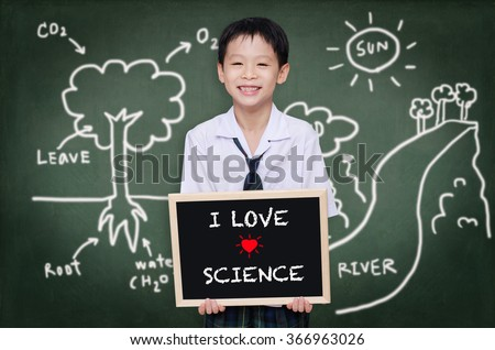 Asian schoolboy in uniform standing in front of chalkboard  - stock photo