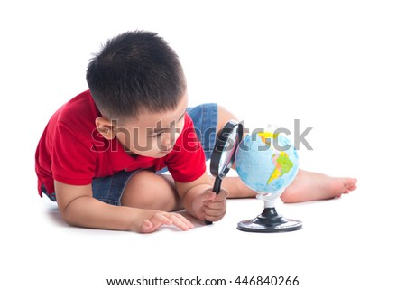 Asian schoolboy with a magnifying glass carefully examines the globe isolated on white background.