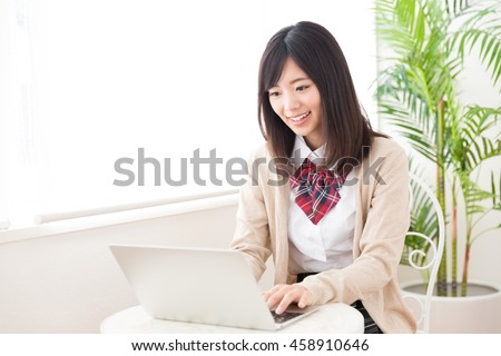 asian schoolgirl using laptop in the cafe