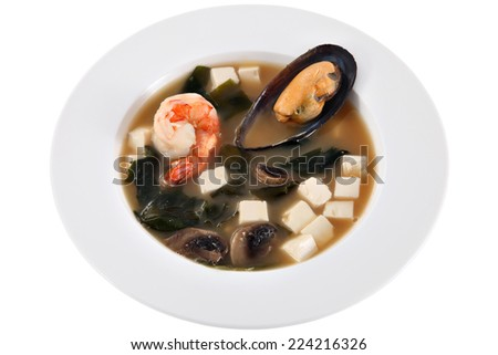 Asian seafood soup with cubes of cheese prawns and mussels in the shell, isolated on white background. - stock photo