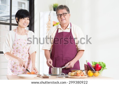 Asian senior couple preparing food at kitchen. Seniors living lifestyle at home. - stock photo