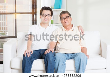 Asian senior father and adult son at home. Family living lifestyle. - stock photo