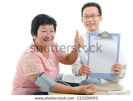 asian senior female thumbs up during medical checkup with doctor ,south east asian chinese ethnicity - stock photo
