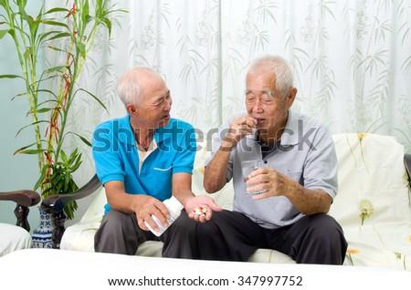 Asian senior man having medicine at home. Adult son caring for a senior man. - stock photo