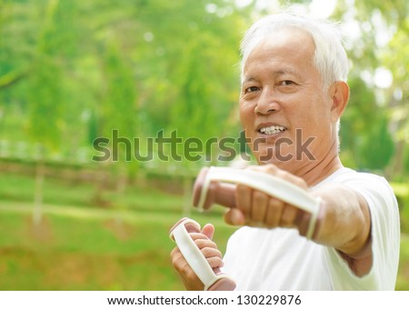 Asian senior man healthy lifestyle. Happy Asian grandparent playing sport at outdoor green park. - stock photo