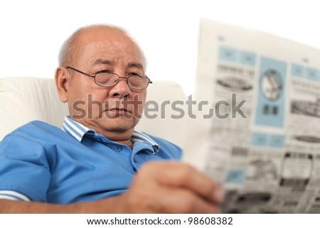 Asian senior man reading newspaper on white background - stock photo