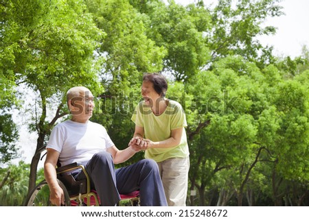 Asian senior man sitting on a wheelchair with his wife - stock photo