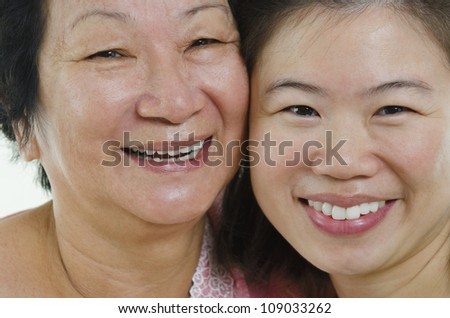 Asian senior mother and adult daughter face close up - stock photo