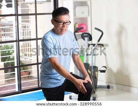 asian senior with knee injury during a gym workout - stock photo