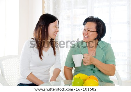 Asian senior woman and daughter having tea time