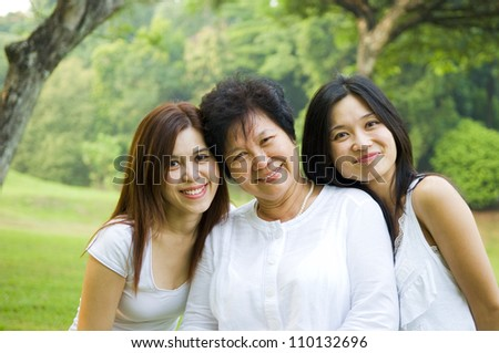 Asian senior woman and daughters enjoying the outdoors - stock photo