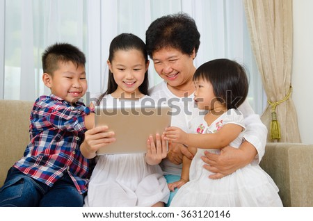 Asian senior woman and grandchildren having fun with tablet computer - stock photo