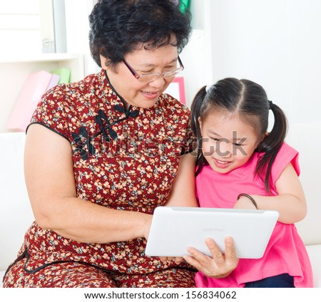 Asian senior woman and granddaughter using tablet computer - stock photo