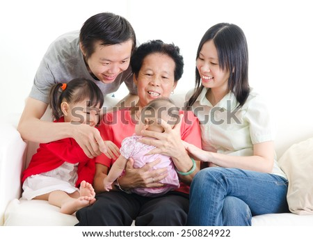 Asian senior woman holding her new born grandchild enjoying the precious moments with family. - stock photo