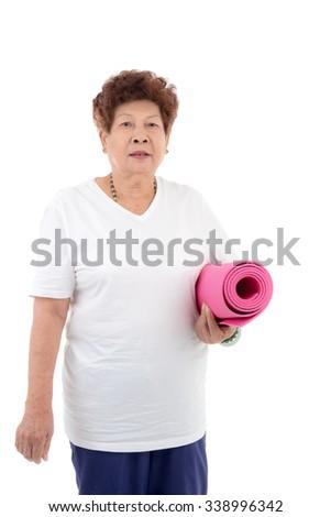 Asian senior woman holding pink yoga mat - stock photo