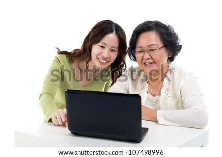 asian senior woman learns to use computer - stock photo