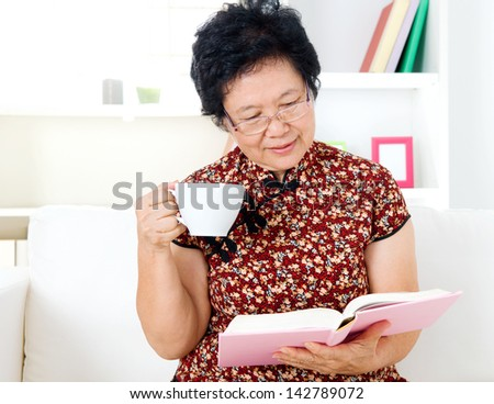 Asian senior woman reading - stock photo