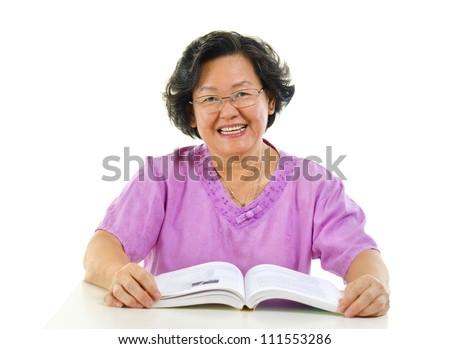 Asian senior woman reading book over white background - stock photo