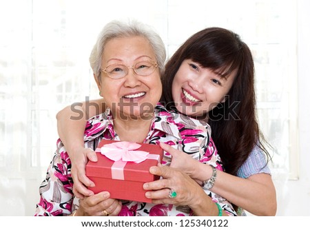 Asian senior woman receiving gift from daughter - stock photo