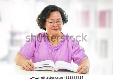 Asian senior woman serious reading book at home - stock photo
