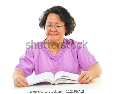 Asian senior woman serious reading book over white background - stock photo