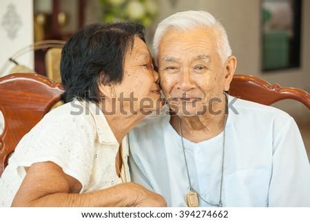 Asian Senior womman kissing senior man at home - stock photo