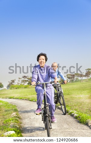 asian seniors couple biking in the park - stock photo