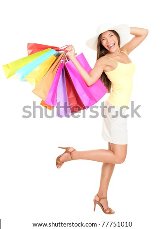 Asian shopping woman happy smiling holding many shopping bags. Asian shopper girl isolated on white background in full length wearing summer hat. - stock photo