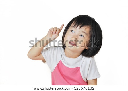 asian small girl child pointing at something above her against a white background - stock photo