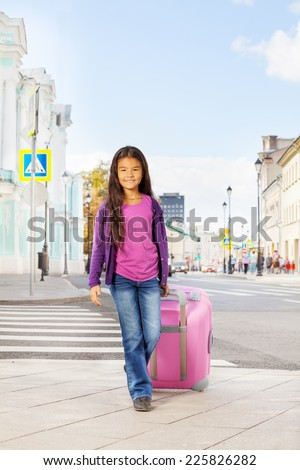 Asian small girl holding pink luggage on  street - stock photo
