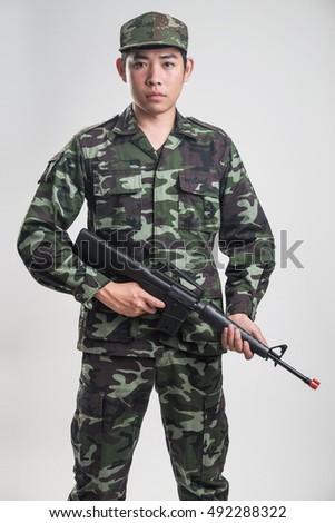 Asian soldier in green camouflage uniform with long gun