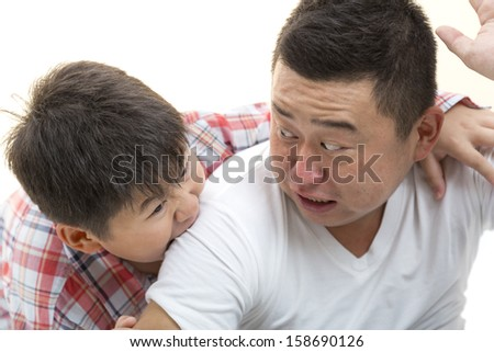Asian son biting father shoulder while playing on isolated white background
