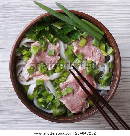 Asian soup pho bo with beef, rice noodles and vegetables close-up. top view  - stock photo