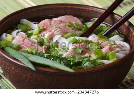Asian soup with beef, rice noodles and fresh herbs in a bowl. Close-up of a horizontal  - stock photo