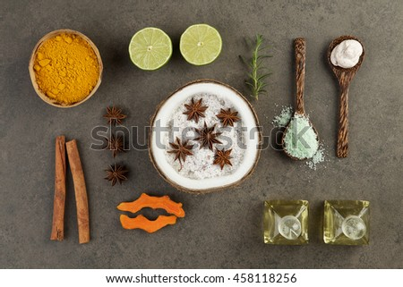Asian spa setting with coconut, turmeric, lime, cinnamon, anise, scrub, salt sea, rosemary and oil on rustic background - stock photo