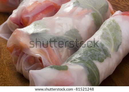 Asian spring rolls in rice paper on a wooden plate.