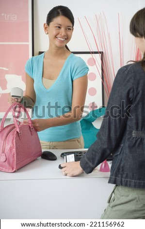Asian store clerk ringing up purchase - stock photo