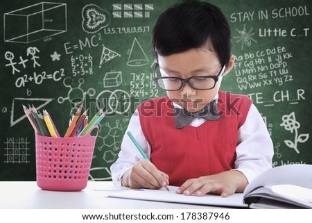 Asian student boy is writing on paper in classroom - stock photo