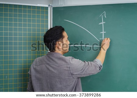 Asian student drawing a graph on a chalkboard with his back to the camera in an educational concept - stock photo