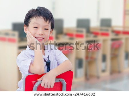 Asian student in uniform smiling in computer room at school - stock photo