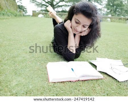 Asian student lying on grass and studying. - stock photo
