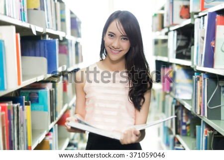 Asian student opening the book in the library - stock photo