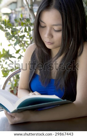 Asian student reading a book - stock photo