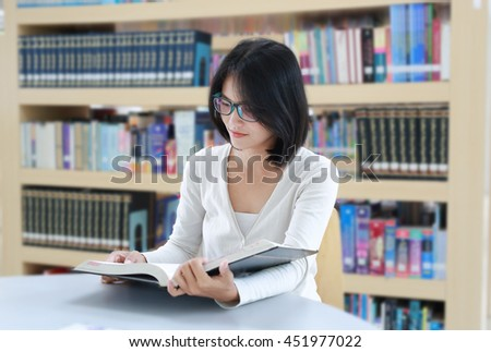 Asian student reading book in the library at university - stock photo