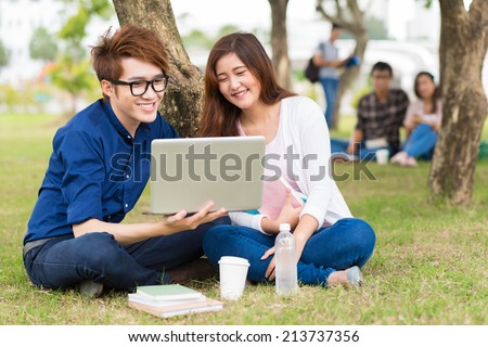 Asian student showing something funny on the laptop to his girlfriend - stock photo