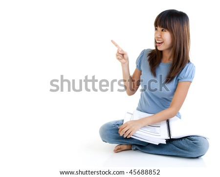 Asian student sitting on floor, pointing to empty space, ready for text. - stock photo
