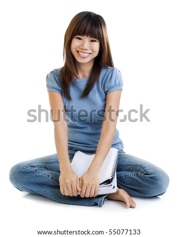 Asian student sitting on floor, with cheerful expression. - stock photo