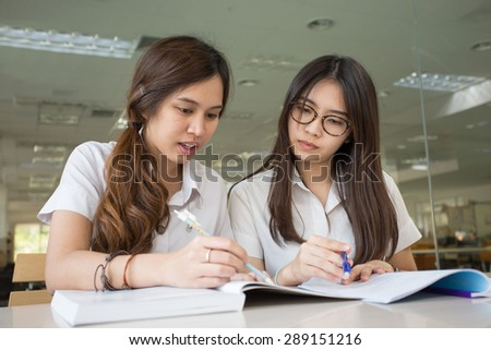 Asian student student discuss in library of university - stock photo