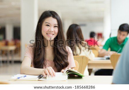 Asian student studying in the library. - stock photo